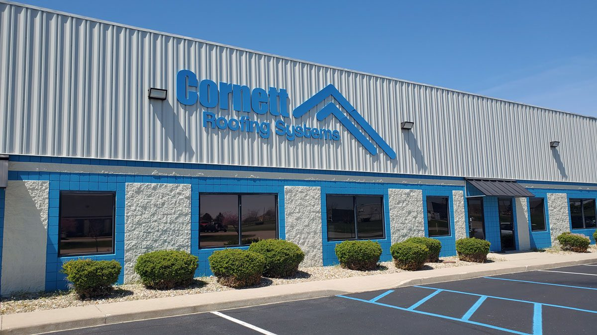 Overview of Cornett Roofing Systems sign and building