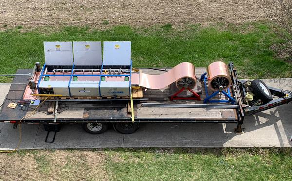 Machine used to roll form standing seam panels on flatbed