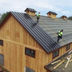 Cornett Roofing workers installing standing seam roof on steep barn