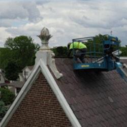 Worker in basket lift repairing a church slate roof