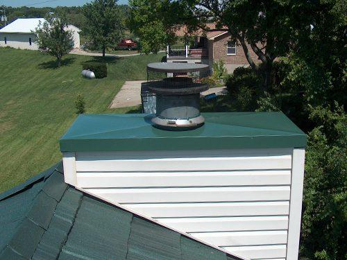 green steel chimney cap on home
