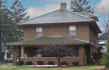 large home with green clay tile roof
